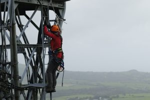Kate climbing transmission tower in North Wales